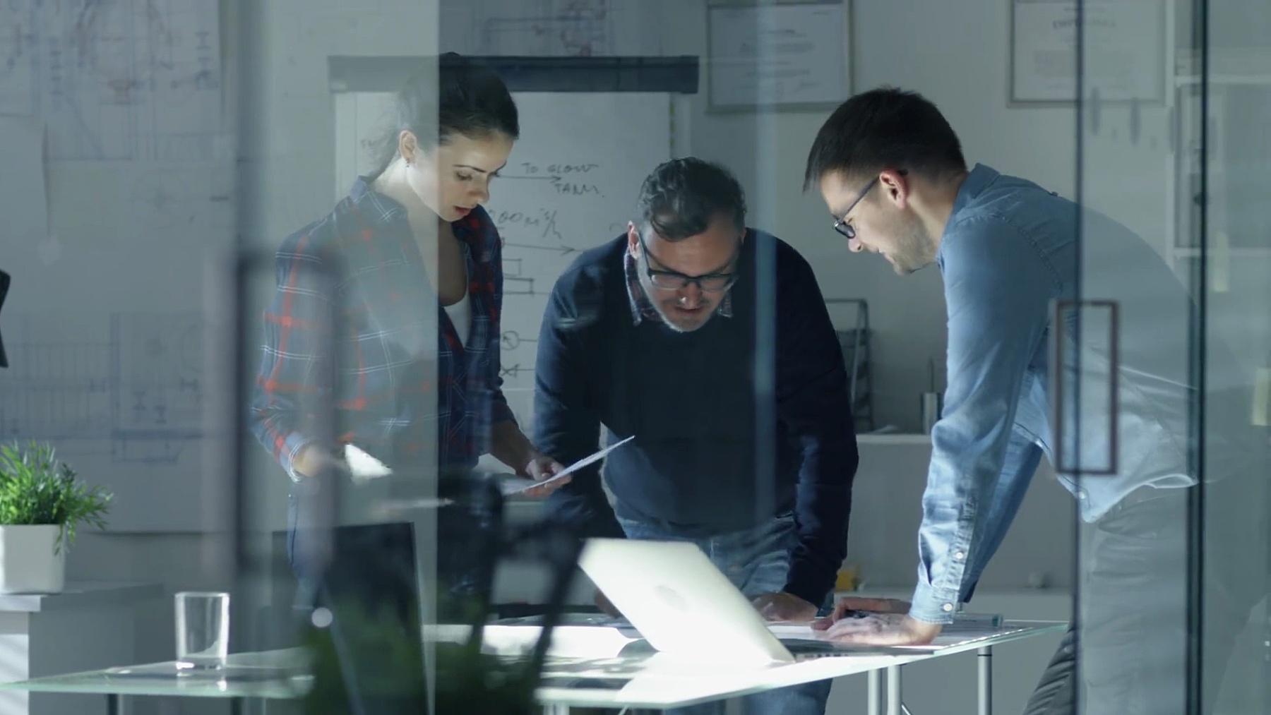深夜设计工程师团队在一个项目上工作。他们在一张照亮的会议桌上工作,上面有文件、蓝图和笔记本电脑。