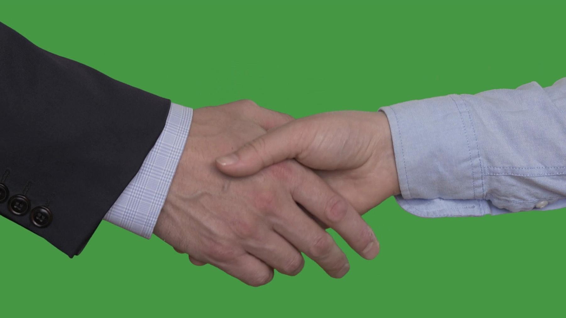 女商人和商人在交易后握手,键控绿屏