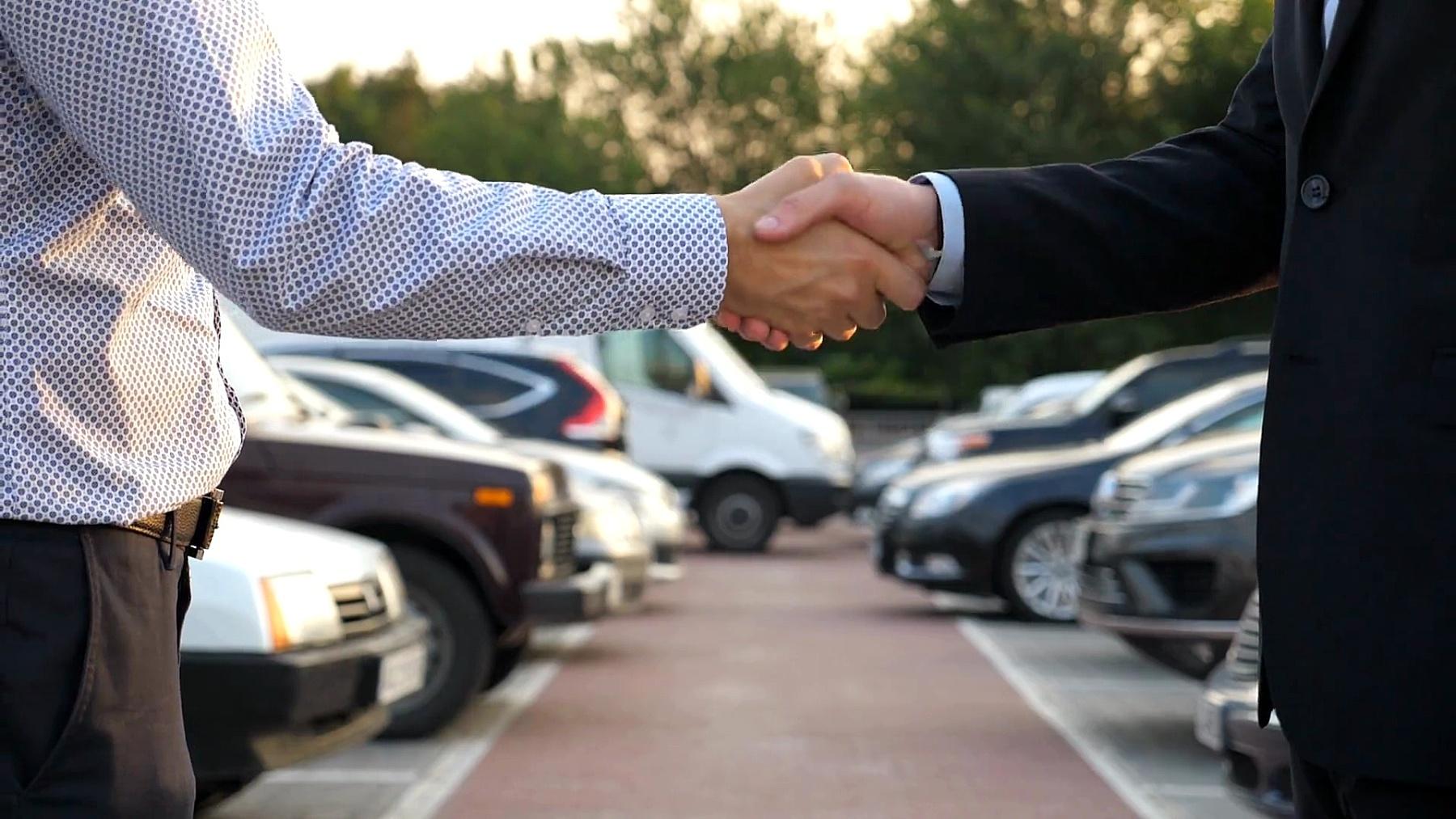 两个面目全非的商人互相握手,背景是停在停车场的汽车。户外经理或客户之间的握手。伙伴们在外面握手。关闭慢动作侧视图