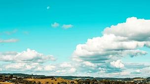乡村山丘上形成复古色彩的白云。在绿松石天空的背景下,奇妙的云的运动。天空中月份的出现。延时