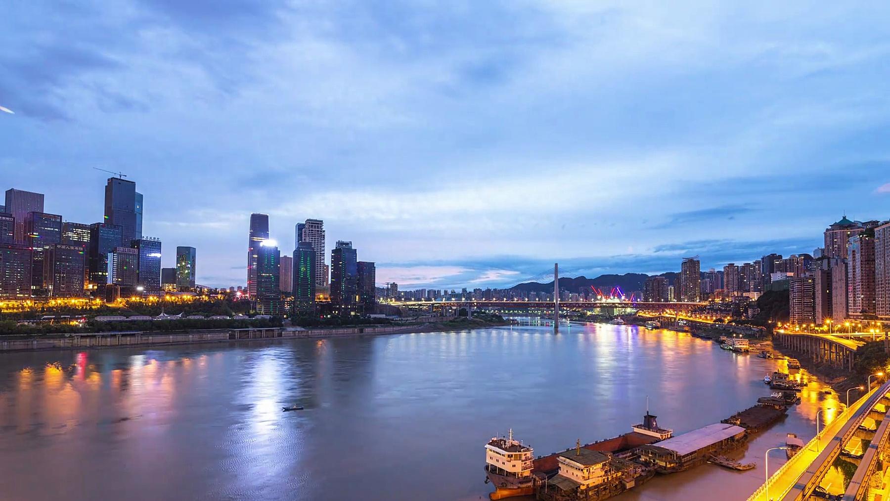 从河边看日出重庆的城市风光和天际线。时间间隔