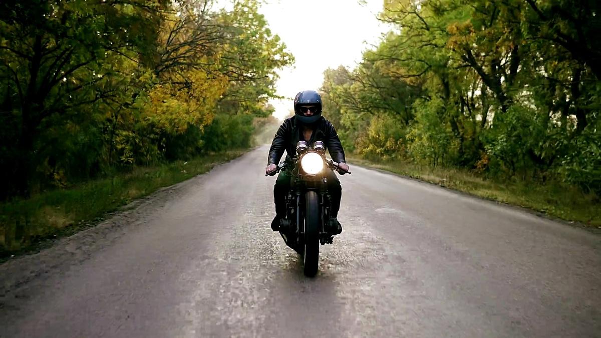 秋天,一个戴着头盔,戴着太阳镜,穿着皮夹克,骑着摩托车在柏油路上的年轻人的前视图。道路周围有棕色和黄色叶子的树