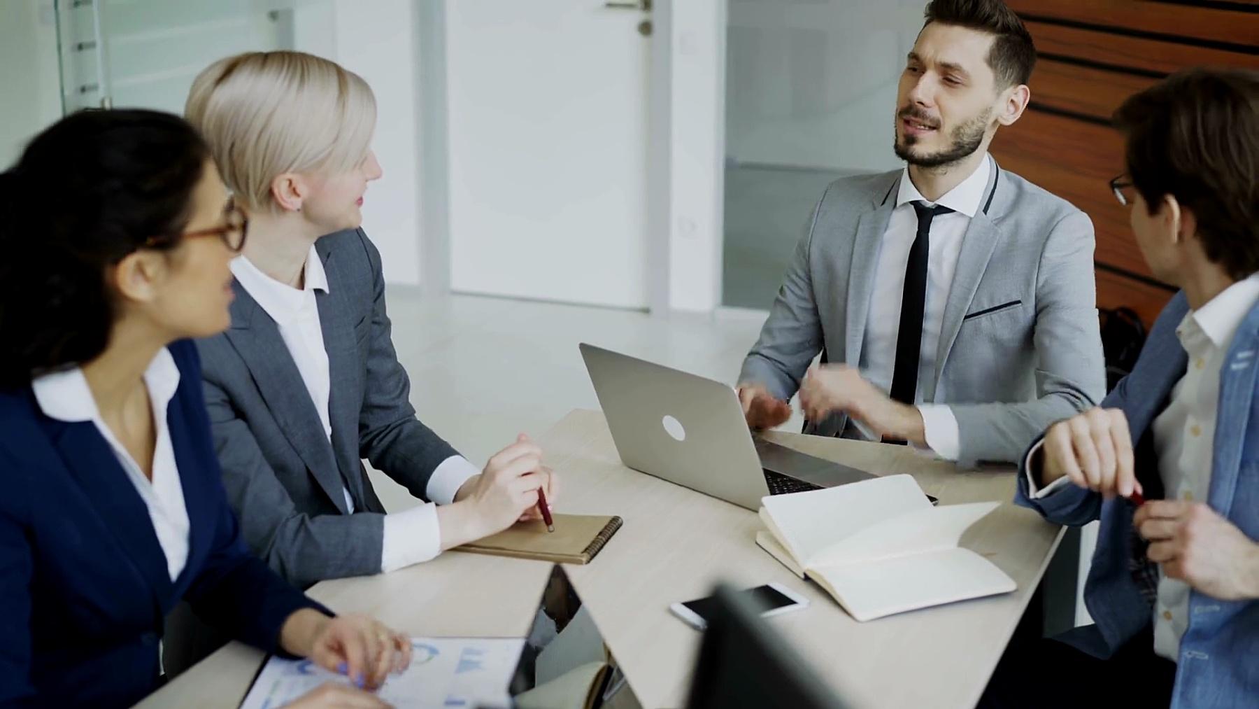 执行经理在办公室会议室与坐在桌子旁的同事讨论业务计划
