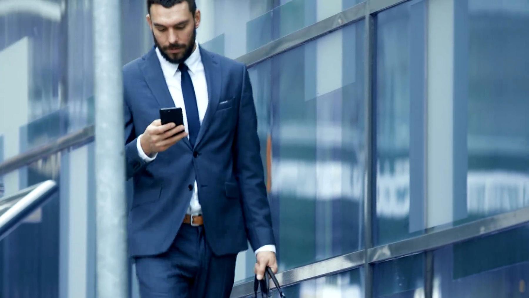 成功的商人在大城市商业区街道上行走时使用智能手机。