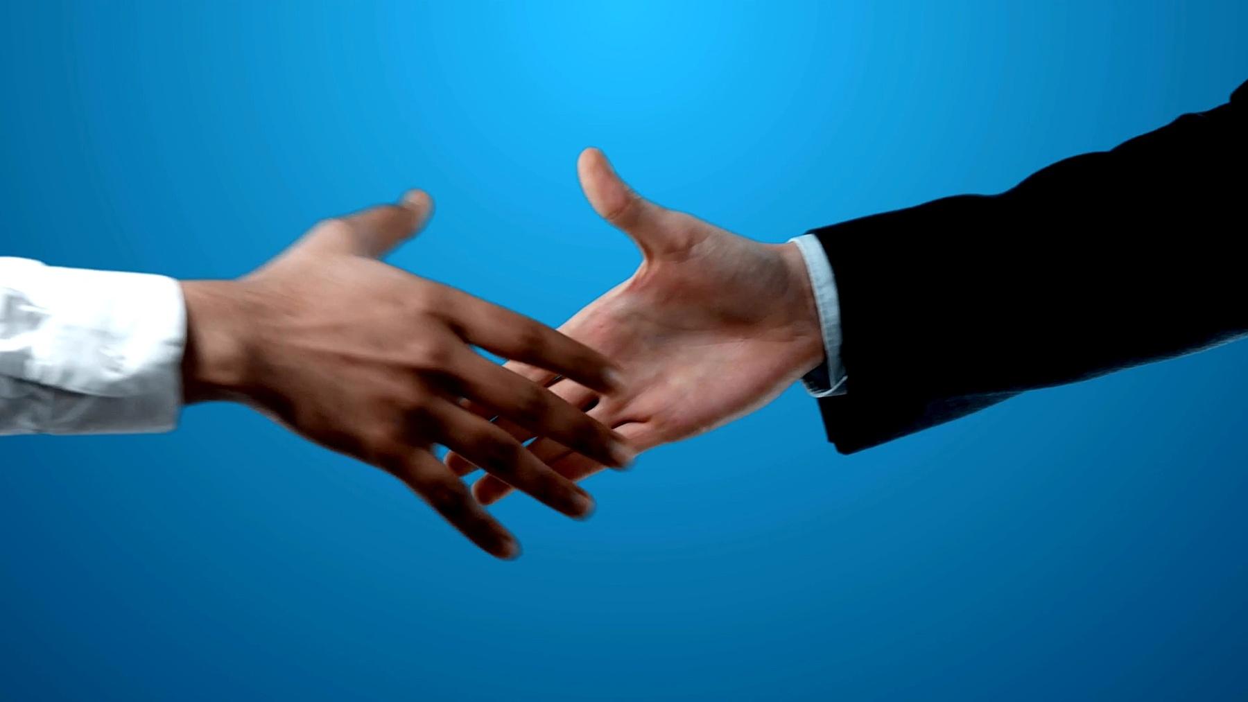 两个身穿西装的商人在Chroma Key  视频上进行国际握手。
