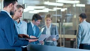 商人在办公室的玻璃里与女商人进行笔记本电脑交谈,讨论与业务相关的问题。忙碌的商务人士走过公司大楼的走廊。