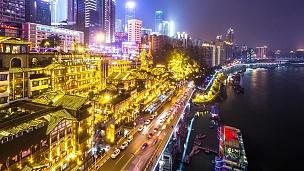 重庆夜晚靠近河流的现代建筑。延时