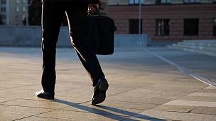 带着公文包走在城市街道上的年轻商人的脚。商人通勤上班。穿西装的自信的家伙在上班的路上。城市景观背景。慢动作后视图特写