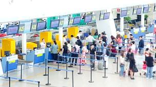 机场旅客人群在柜台大厅办理登机手续延时