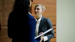 两位女商人同事在现代办公室交谈