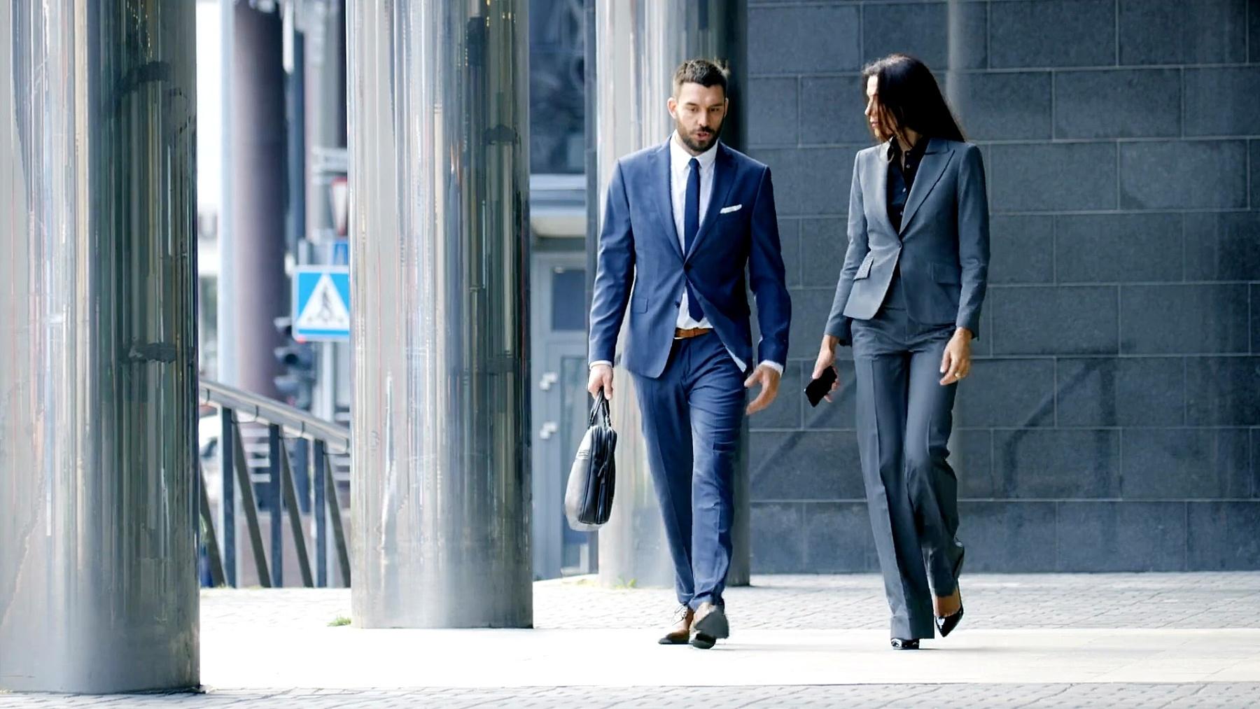 男性和女性商务人士走来走去,讨论财务问题。他们在中央商务区工作。