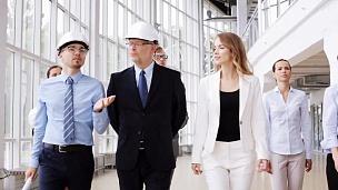 业务团队戴着头盔,办公室里有蓝图