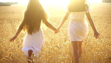 两个女孩一起在麦田上跑步