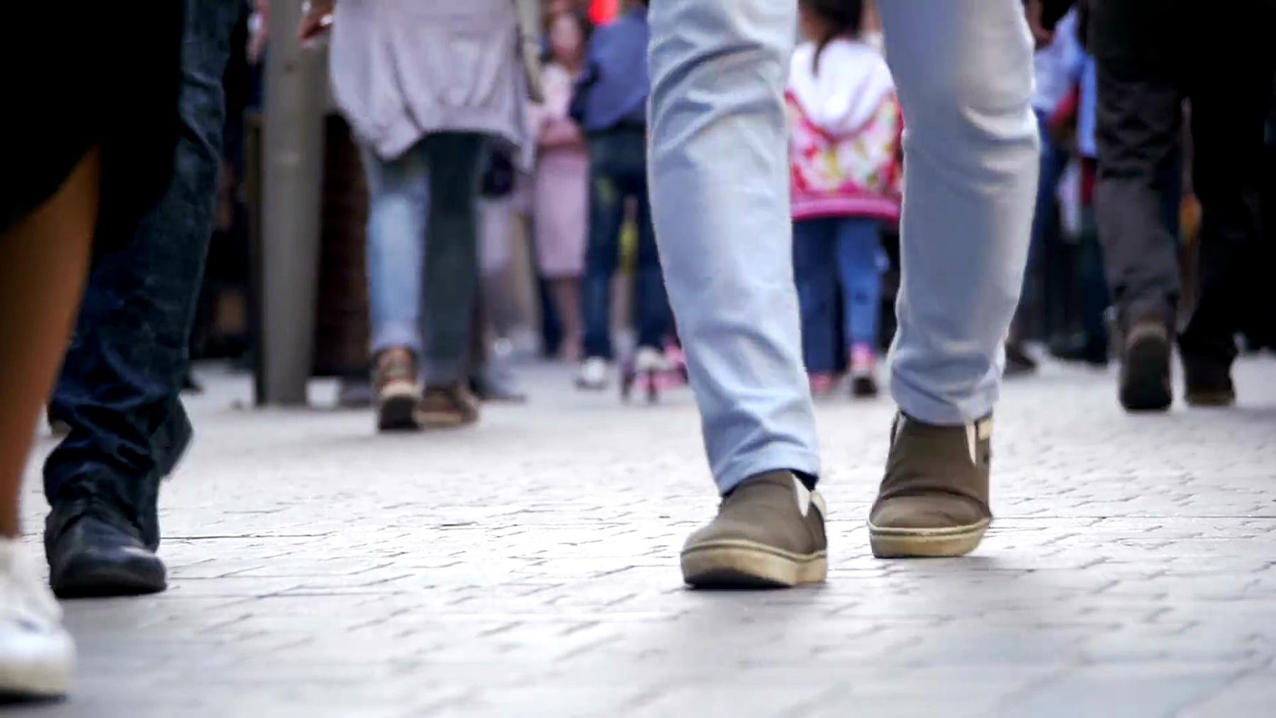 人群匿名者走在街上。人群脚。慢动作
