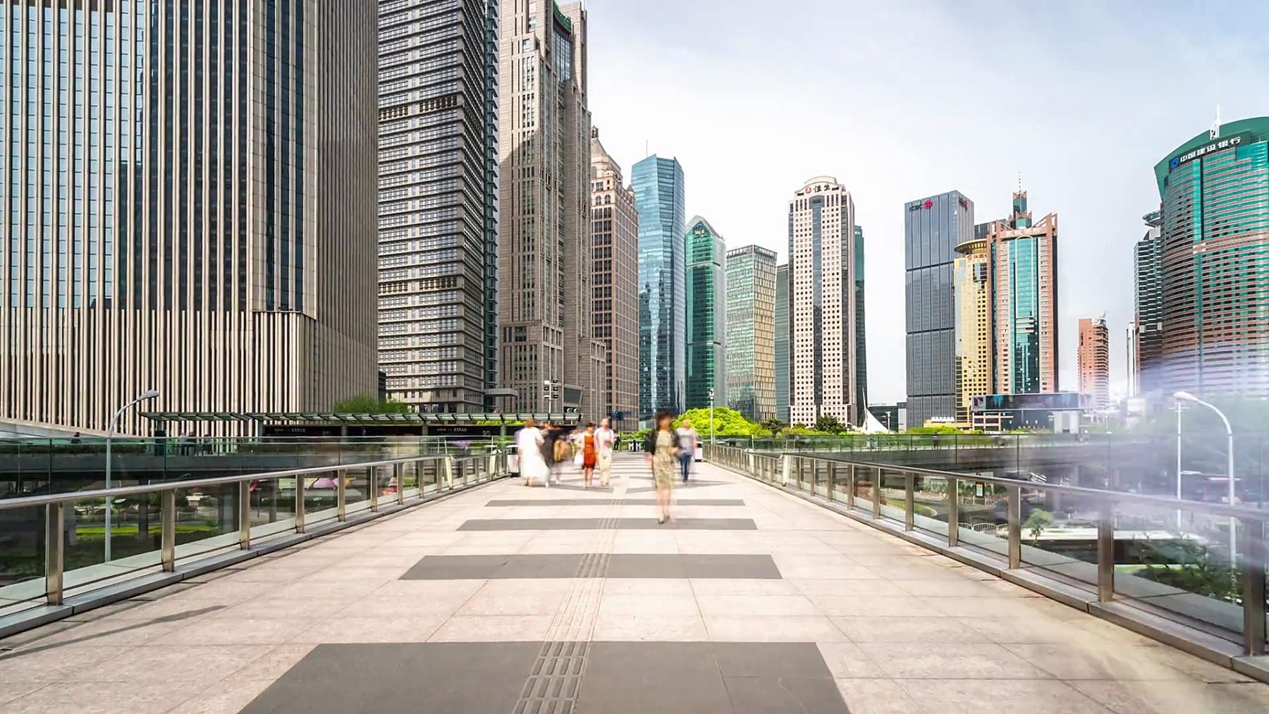 在现代城市中,人行道上挤满了穿过现代建筑的人。延时