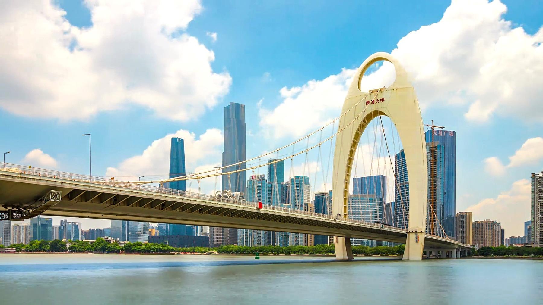 广州广州塔附近的现代桥在蓝云的天空中。时间延迟/中国广州。