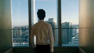 从办公室窗口看城市风光的商人