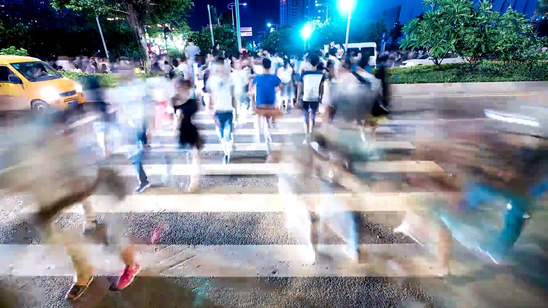 行人在城市广州街道的斑马线上行走,延时摄影。