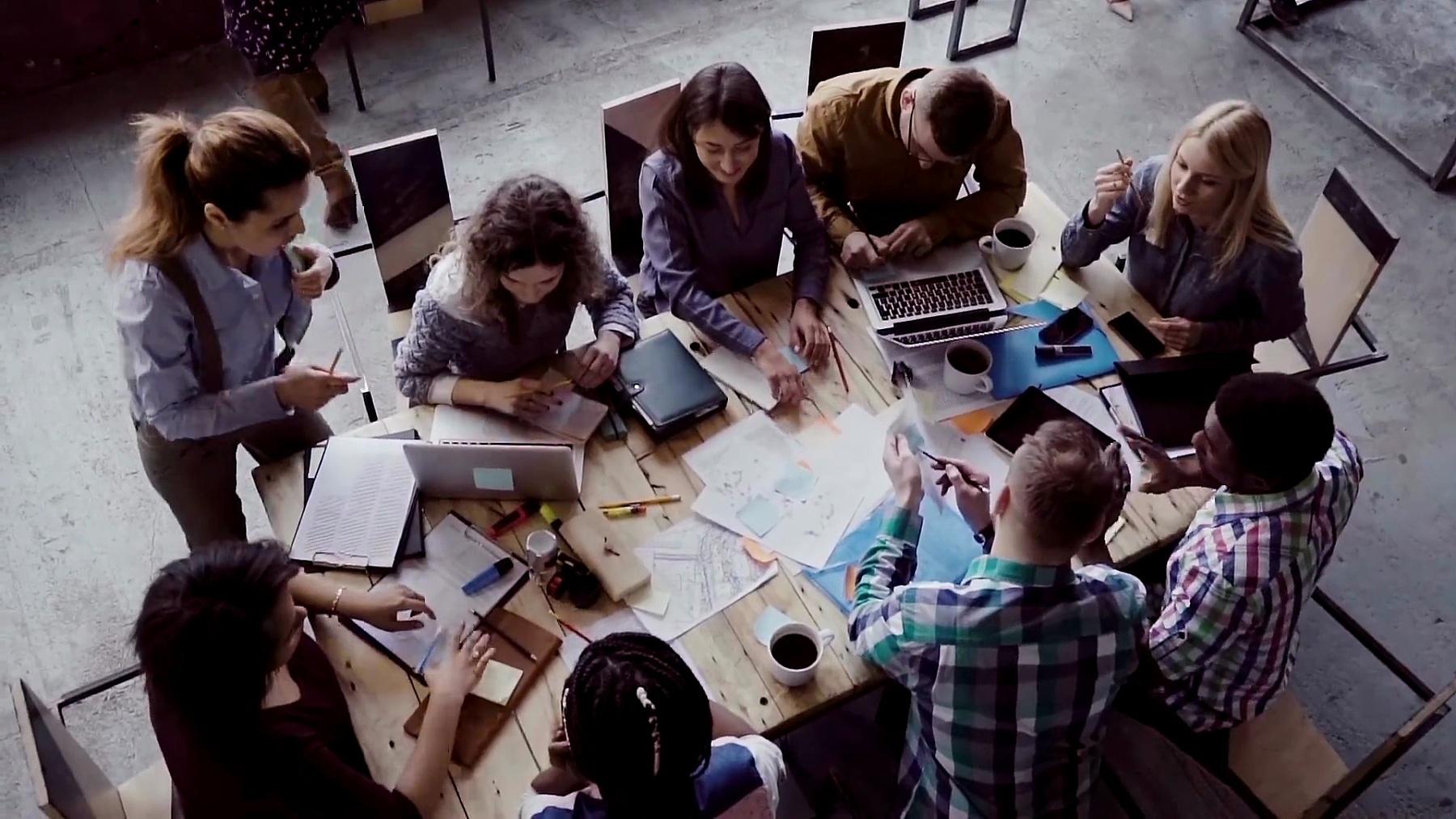 现代办公室的商务会议。多种族群体在桌子附近一起工作的俯视图。慢动作
