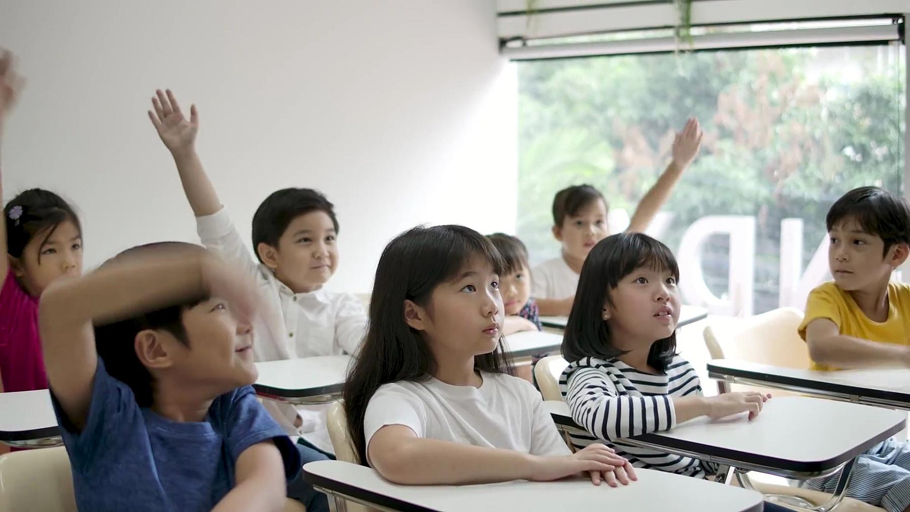一群快乐的亚洲小学生在课堂上举起手臂回答老师的问题。幼儿园学前概念。