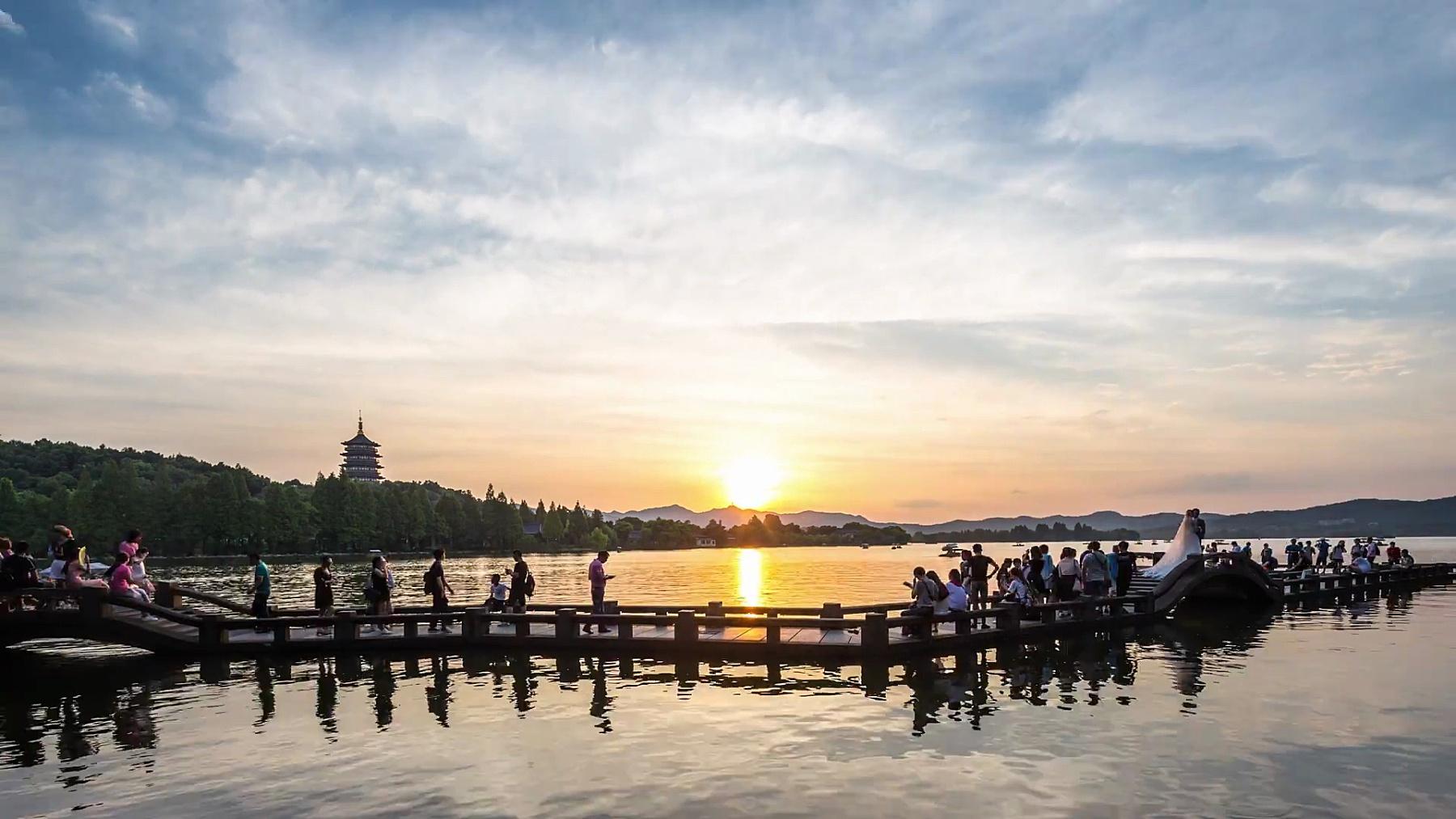 日落时湖上的风人行天桥在云天中时间的流逝