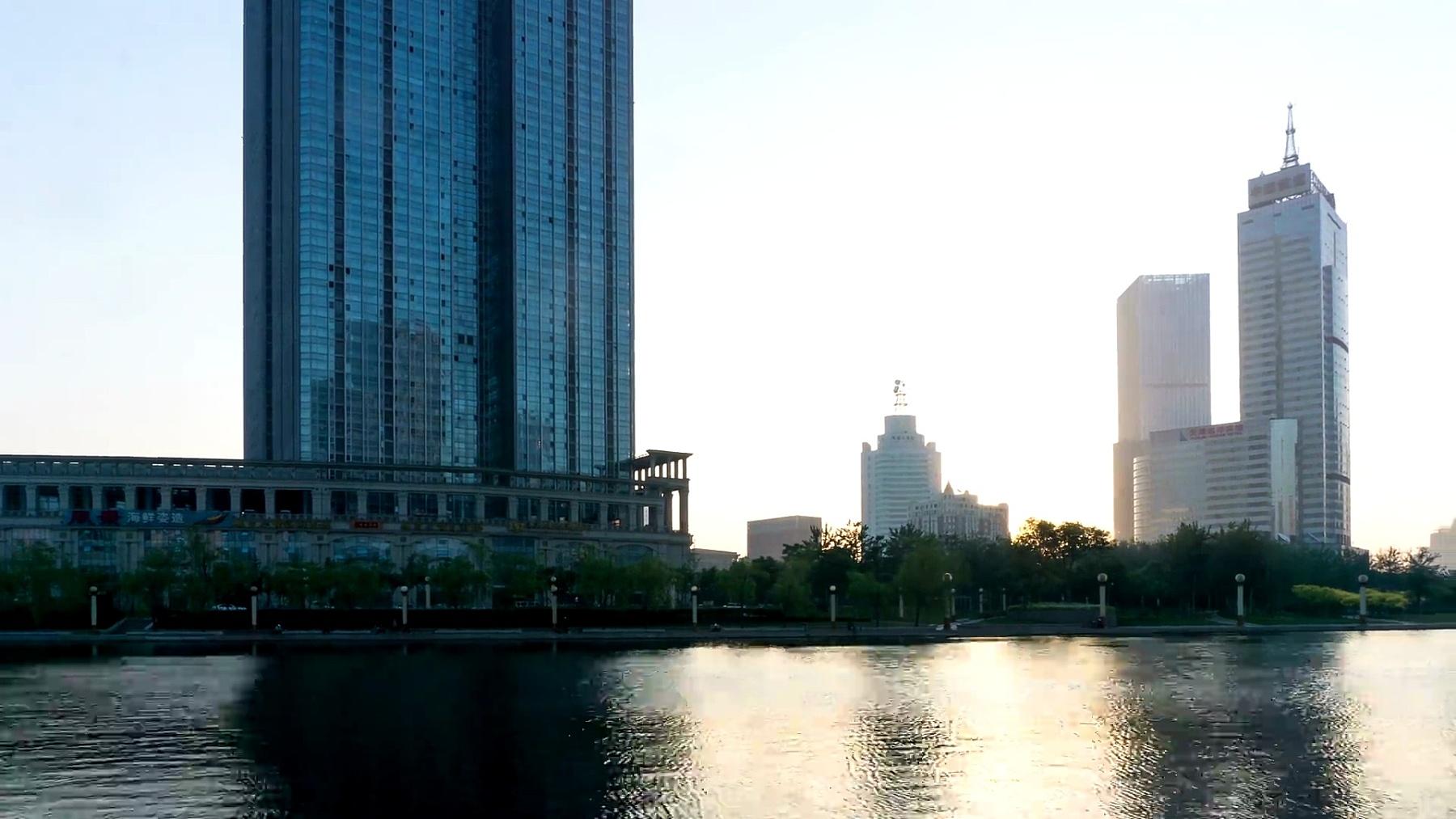 日出时天津河岸的天际线和现代建筑,延时摄影。