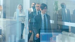 多元文化的商业人群穿过公司大楼的走廊。人们做生意,交谈,合作,谈判和解决问题。