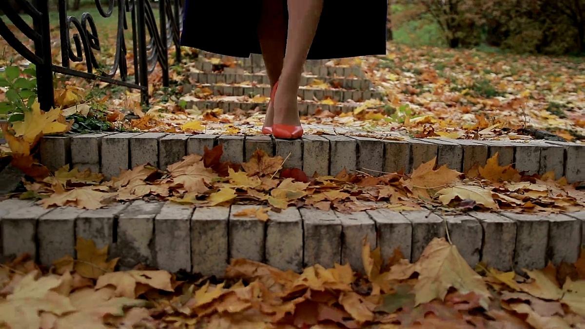 女性穿高跟鞋的腿在秋天走下楼梯
