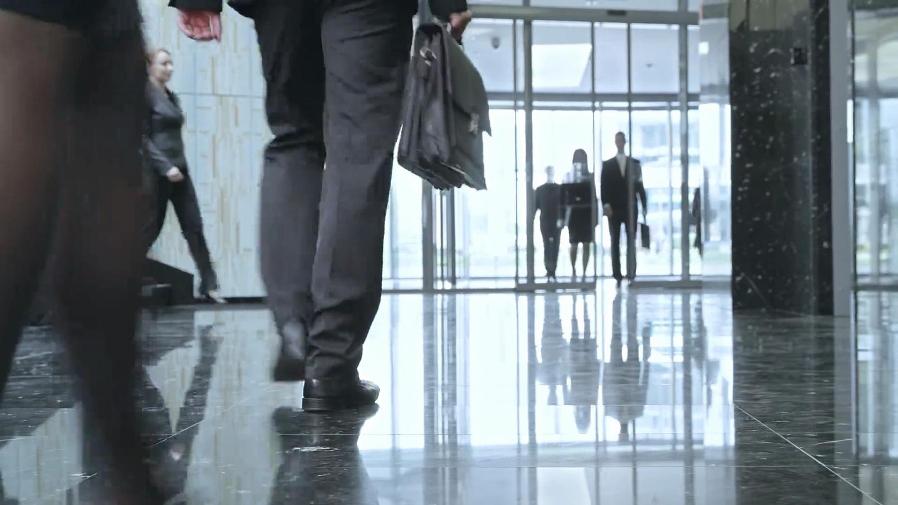 忙碌的商务人士匆匆穿过公司大楼大堂