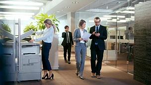 商务人士在走廊里行走和交谈,商务人士在办公室里交谈,使用台式电脑。公司办公室有许多忙碌的员工。