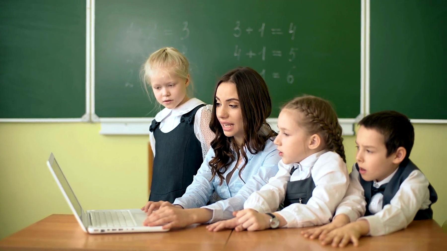 孩子们和老师在教室里讨论和看笔记本电脑