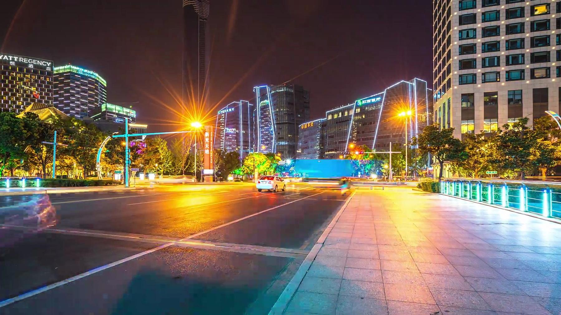 繁忙的道路与现代城市中心区的现代建筑在夜间消逝