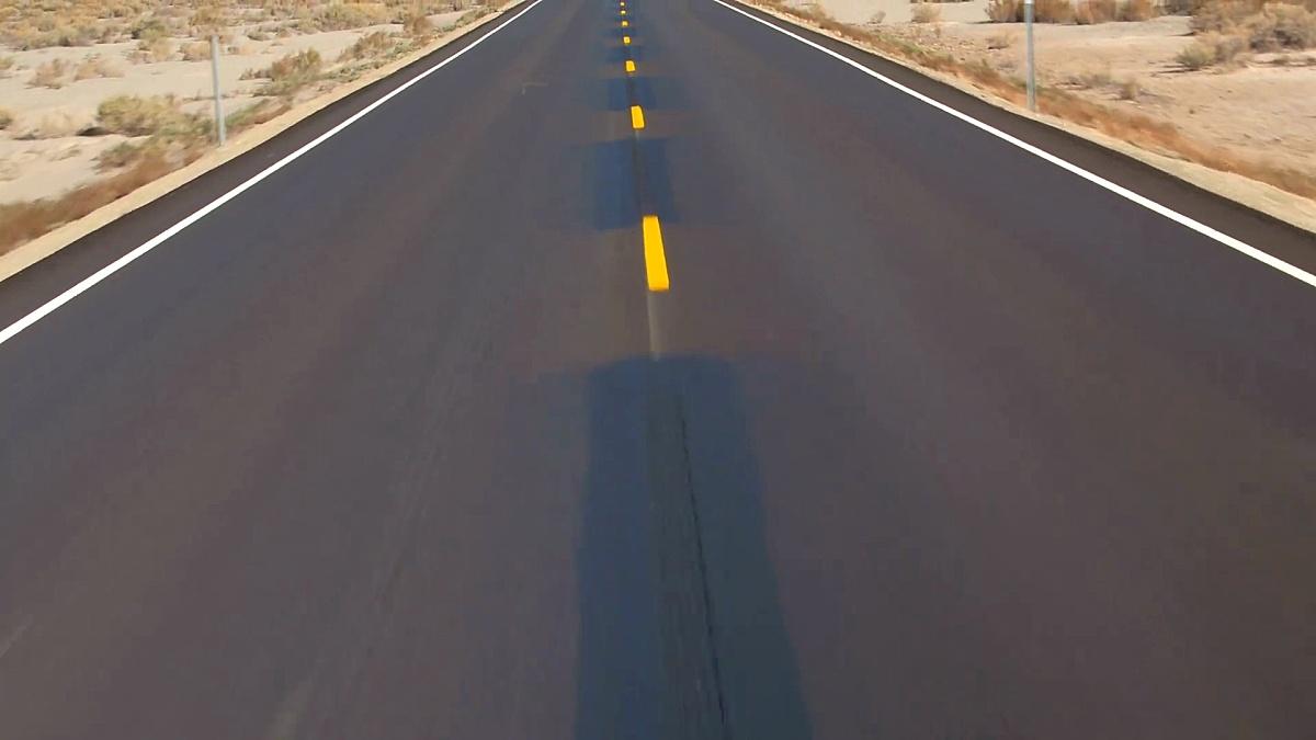 美国犹他州秋天空旷的道路上空飞翔,穿越广袤的沙漠