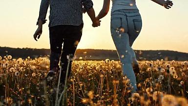 夕阳时分在草地上奔跑的情侣