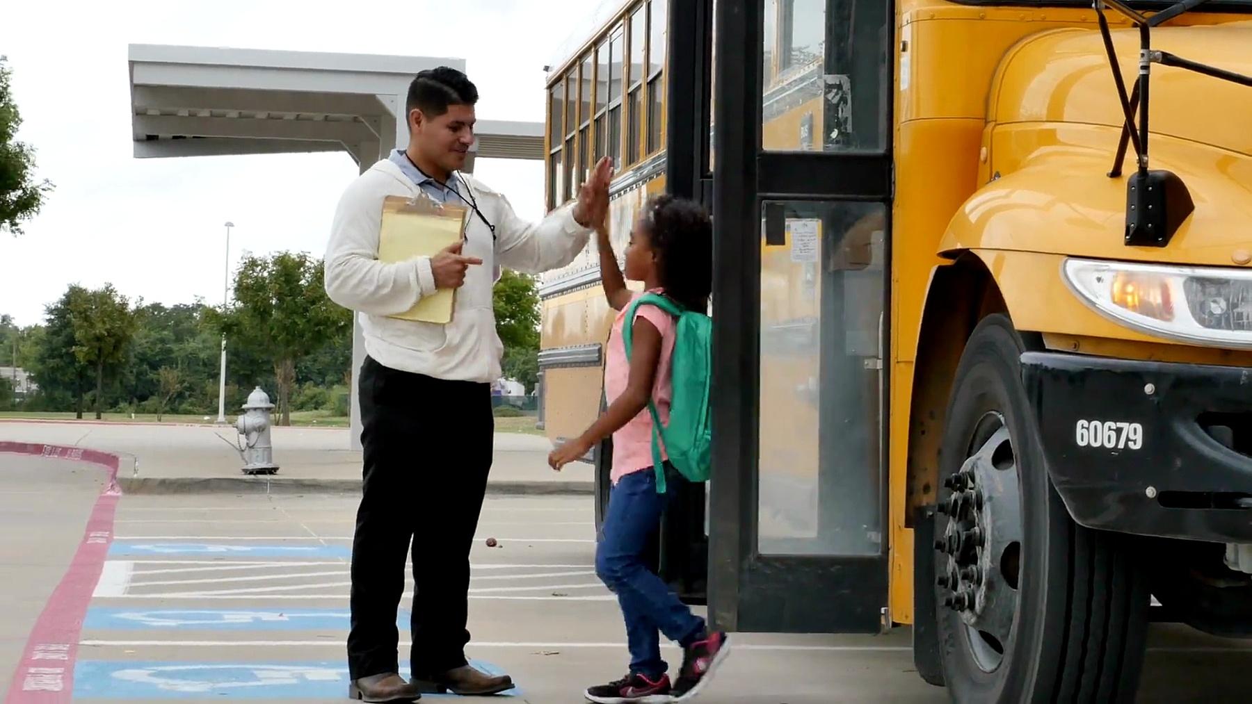 男老师在不同的学童下校车时向他们打招呼
