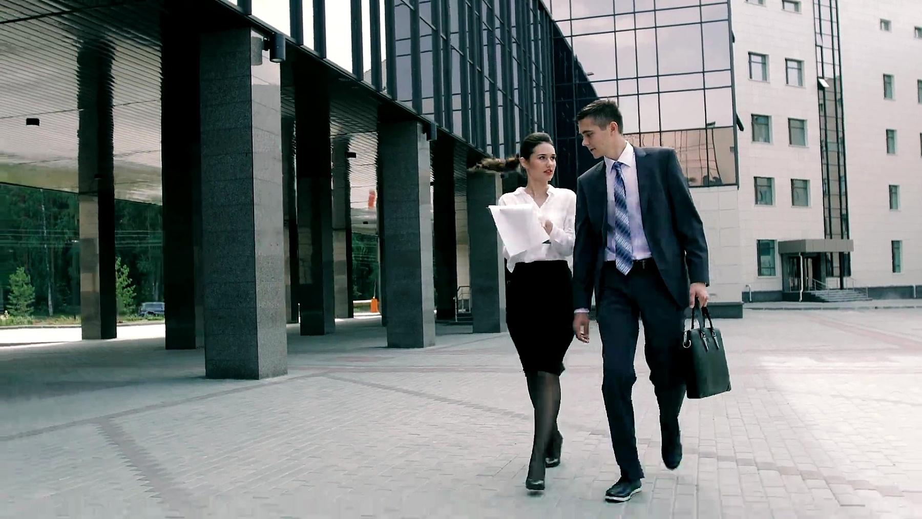 一个成功的商人和他的助手步行去商务中心