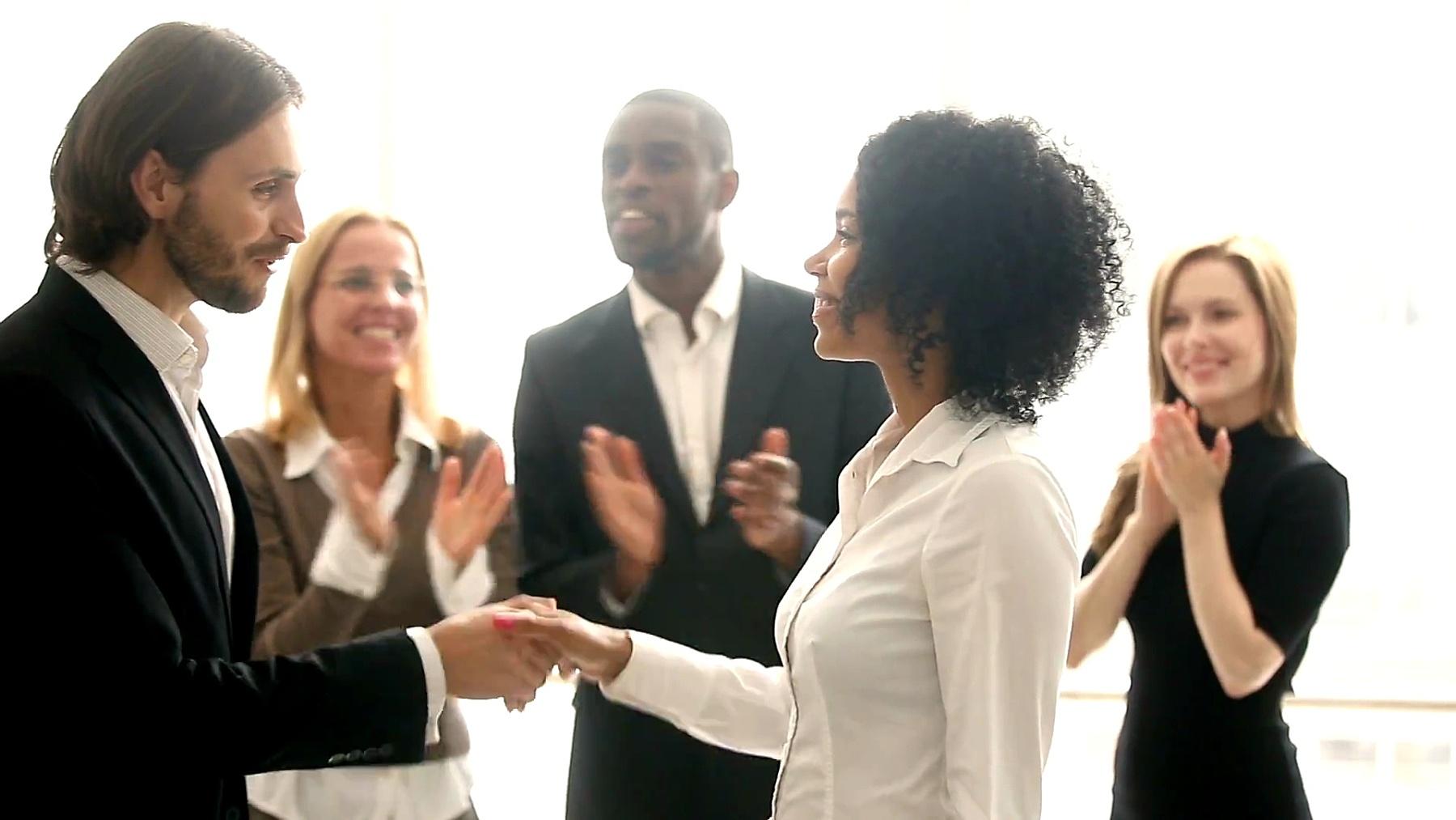 公司老板与非洲员工握手,提拔祝贺黑人年轻女子