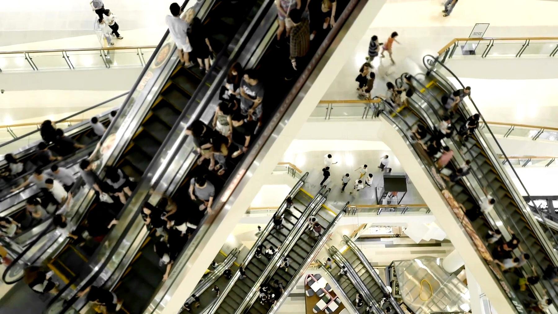 人们在购物中心的自动扶梯上移动
